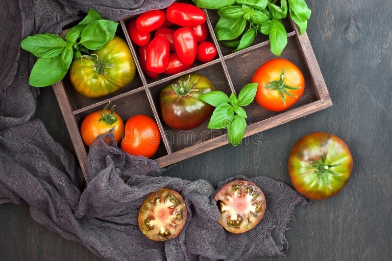 Tomates fraîches et feuilles fraîches de basilic dans la boîte en bois Ing de nourriture photographie stock