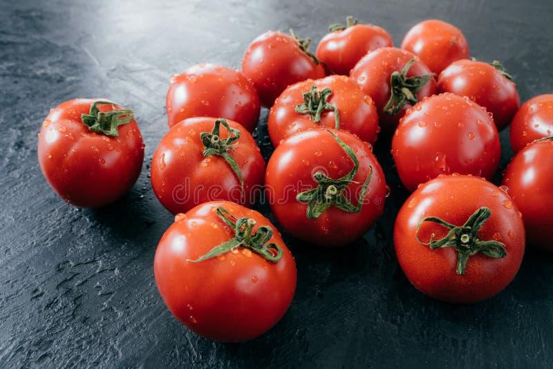 Tomates fraîches mûres rouges savoureuses avec des baisses de l'eau sur le fond foncé Légumes sélectionnés du jardin Nourriture c photos stock
