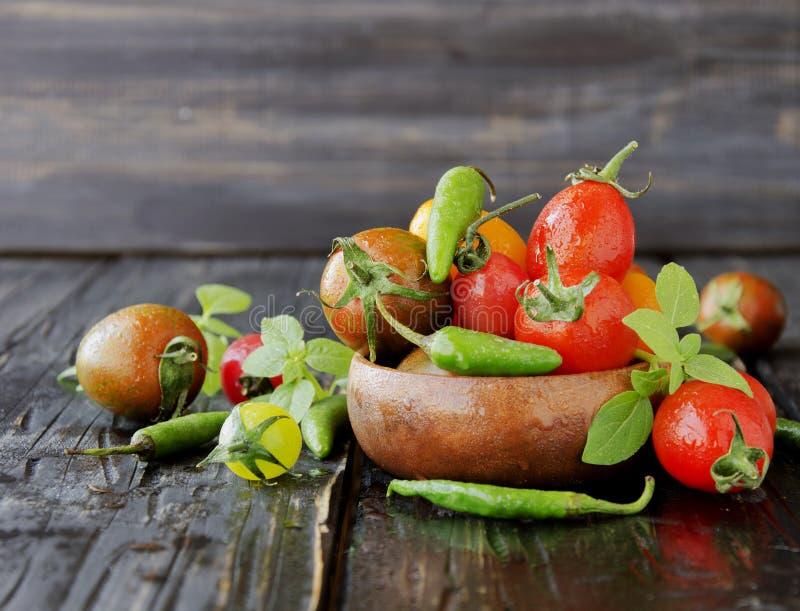 Tomates frescos con albahaca en la tabla de madera, foco selectivo fotografía de archivo