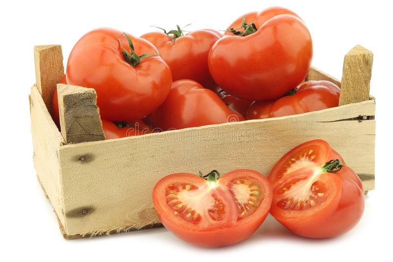 Tomates frescos da carne e cortado em uma caixa de madeira imagem de stock