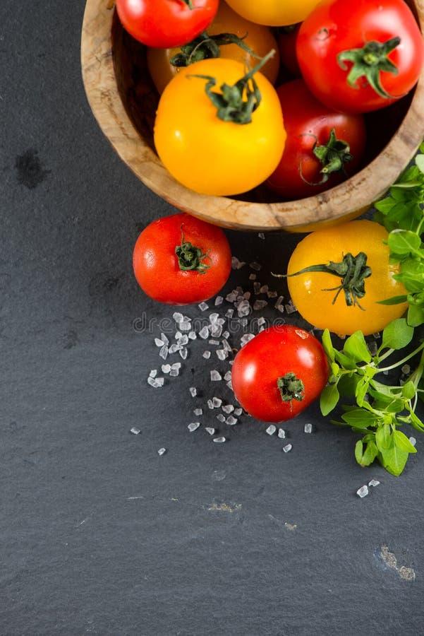 Tomates frescos de la granja con la hierba fresca de la albahaca fotografía de archivo