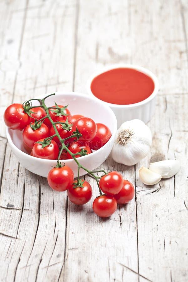 Tomates frescos en el cuenco blanco, la salsa y el ajo crudo en la tabla de madera rústica foto de archivo