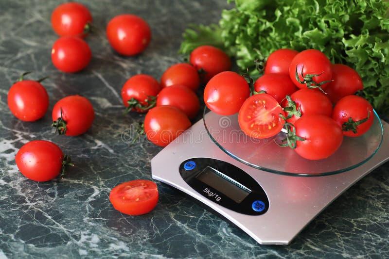 Tomates frescos en el pesaje de las escalas de la cocina fotografía de archivo libre de regalías