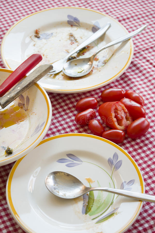 Tomates frescos en una tabla con las placas sucias foto de archivo