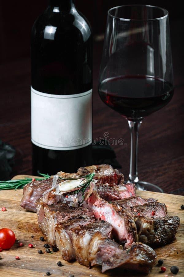 Tomates grelhados cortados do bife do lombo em uma placa de corte com a garrafa do vinho e do copo de vinho imagens de stock royalty free
