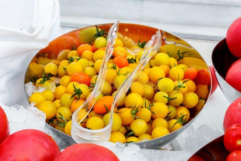 Tomates jaunes et roses dans une cuvette de glace photo stock
