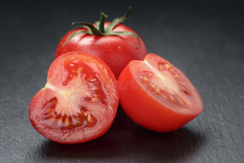 Tomates lavados maduros no fundo da ardósia fotografia de stock