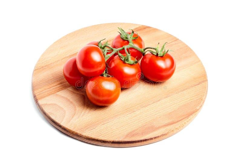 Tomates mûres rouges fraîches sur une branche verte s'étendant sur le hêtre en bois photo stock
