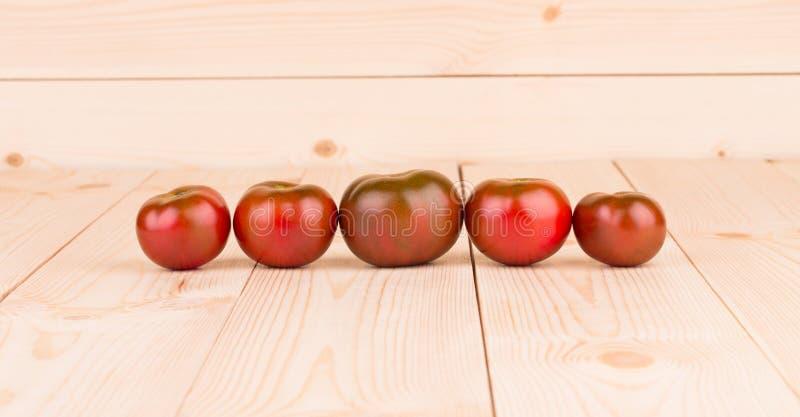 Tomates mûres de kumato sur la table en bois photos stock