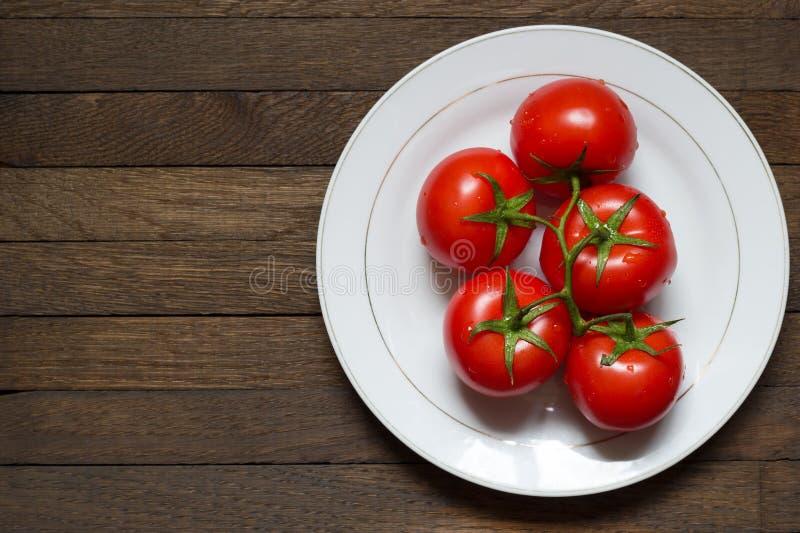 Tomates madurados rojos en rama en la placa blanca en la tabla de madera oscura con el espacio de la copia imagen de archivo