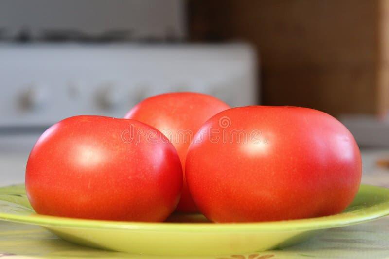 Tomates maduros en un disco fotos de archivo libres de regalías