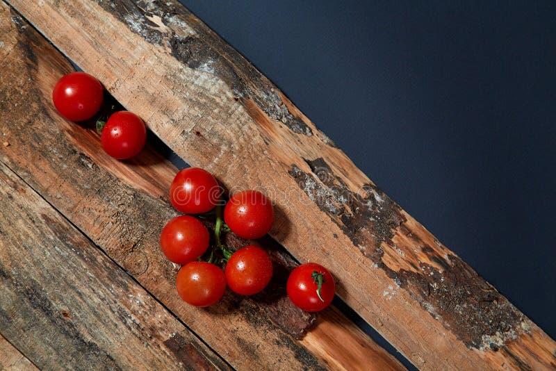 Tomates maduros vermelhos brilhantes no ramo coberto com as gotas da água compostas nas pranchas de madeira foto de stock