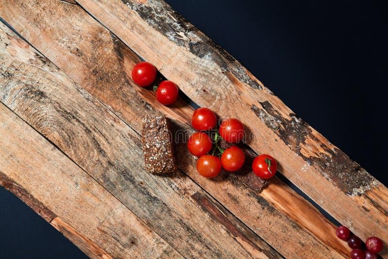 Tomates maduros vermelhos brilhantes no ramo coberto com as gotas da ?gua compostas nas pranchas de madeira fotos de stock