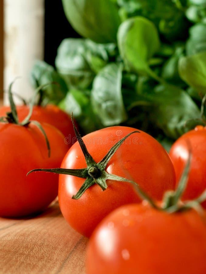 Tomates, manjericão e um frasco do vinho imagens de stock