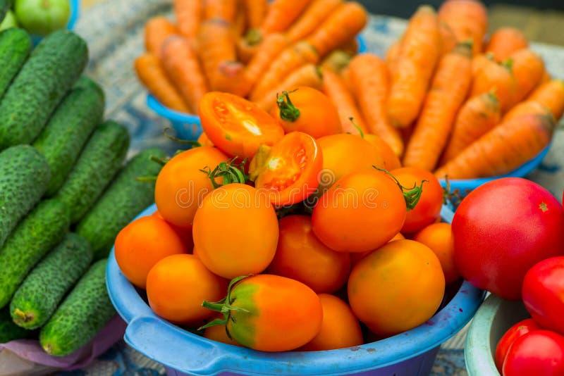 Tomates oranges avec des concombres et des carottes à vendre sur le marché photographie stock