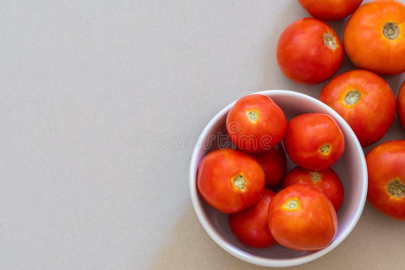 Tomates oranges mûres aux environs de la cuvette blanche images stock