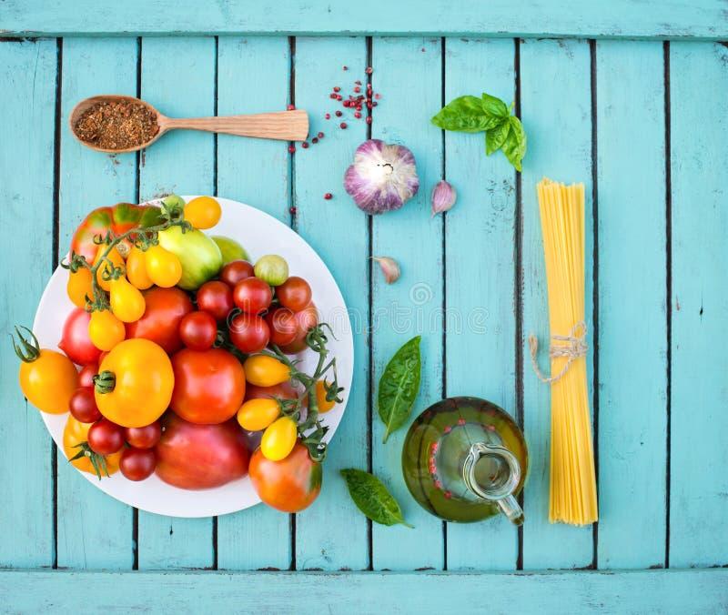 Tomates orgânicos coloridos na placa branca com azeite GA da massa fotos de stock