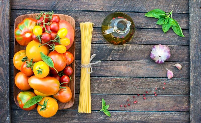 Tomates orgânicos coloridos na placa de madeira com azeite g da massa fotos de stock