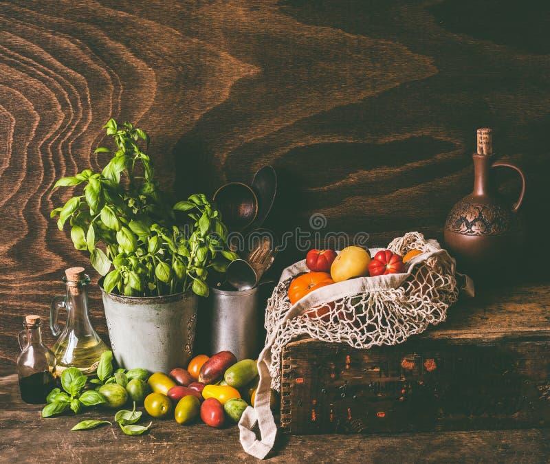 Tomates organiques de ferme colorée dans le panier de crochet avec des ingrédients et des outils de cuisson sur la table de cuisi photos stock