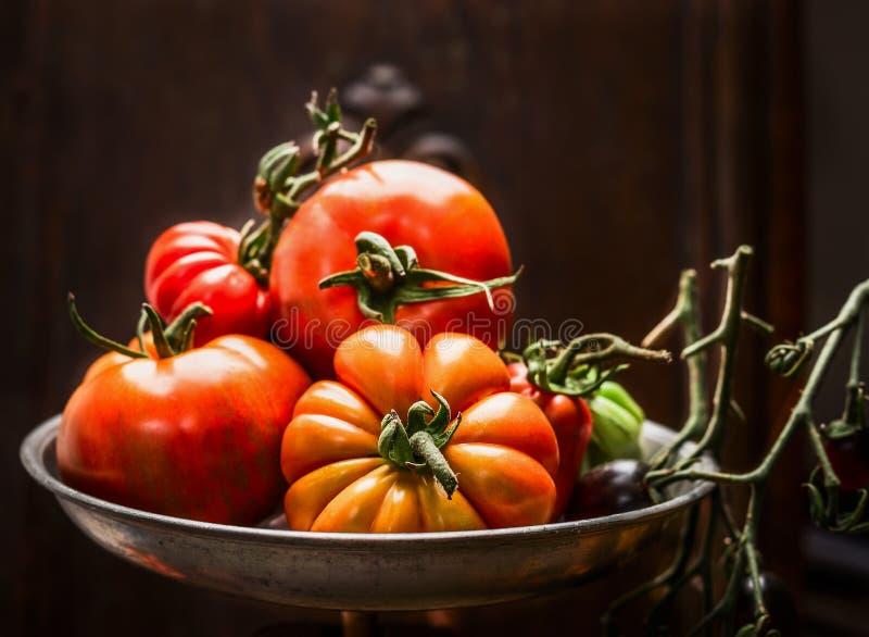 Tomates organiques fraîches de ferme dans la cuvette en acier au-dessus du fond en bois foncé photos stock