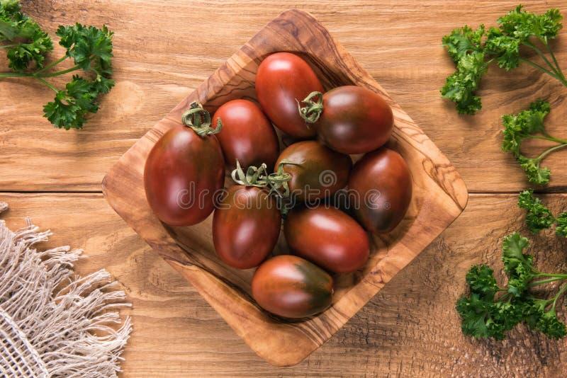 Tomates ovales rouge foncé dans la cuvette en bois naturelle image stock
