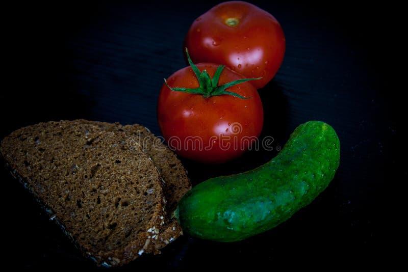 Tomates, pepino y pan en fondo negro fotos de archivo