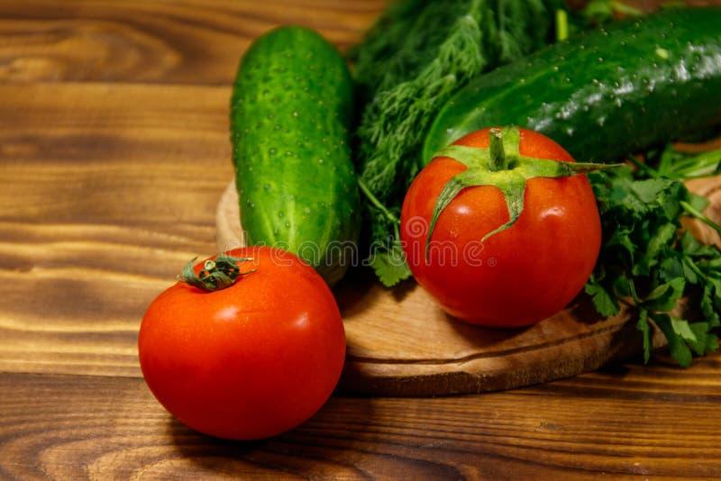 Tomates, pepinos, perejil y eneldo frescos imagen de archivo