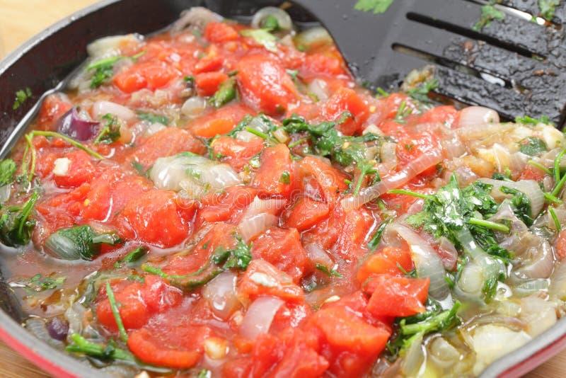 Tomates perejil y el freír de la cebolla foto de archivo libre de regalías