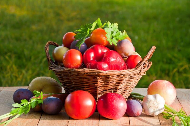 Tomates, pimentas, ameixas, maçãs e outros vegetais e frutos em uma cesta de vime em uma tabela de madeira imagem de stock royalty free