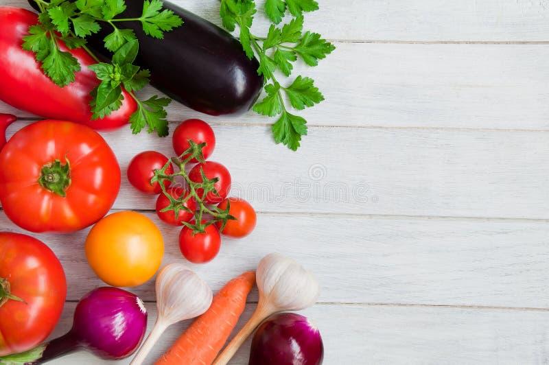 Tomates, pimentas, beringelas e outros vegetais em uma tabela de madeira branca imagem de stock