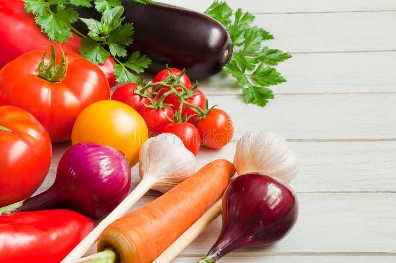 Tomates, pimentas, beringelas e outros vegetais em uma tabela de madeira branca fotografia de stock