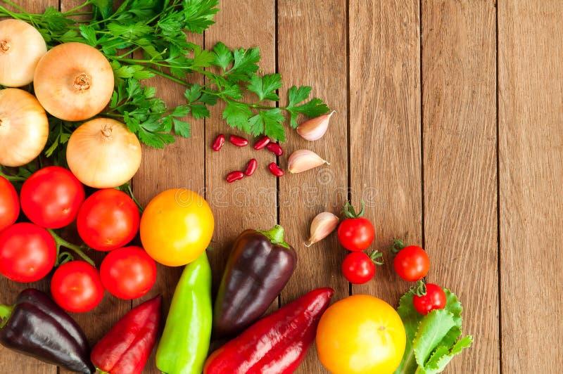 Tomates, pimentas, cebolas em uma tabela de madeira fotos de stock