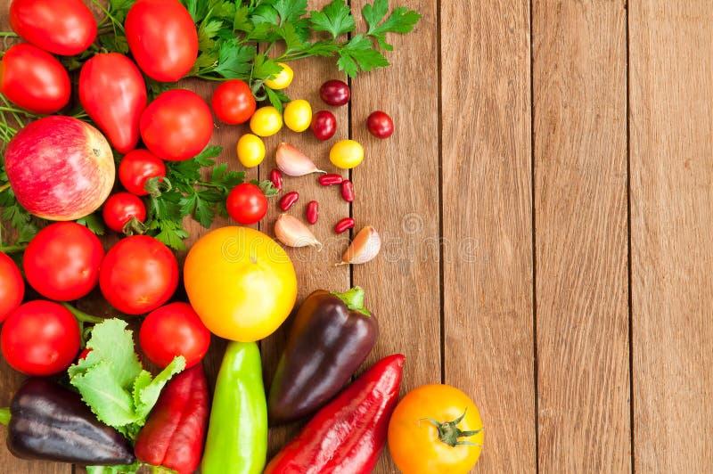 Tomates, pimentas, maçãs em uma tabela de madeira imagem de stock