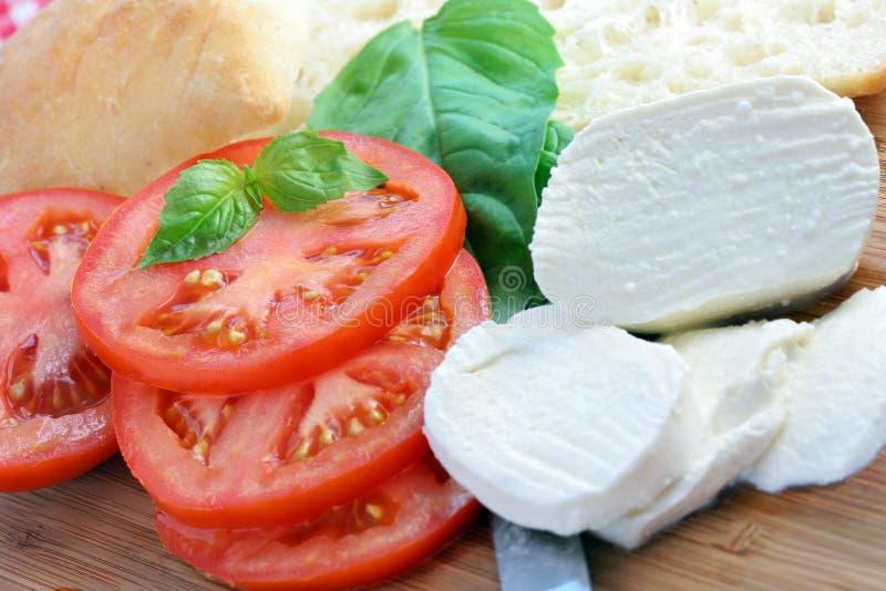 Tomates rebanados, pan y queso fresco de la mozarela imagenes de archivo