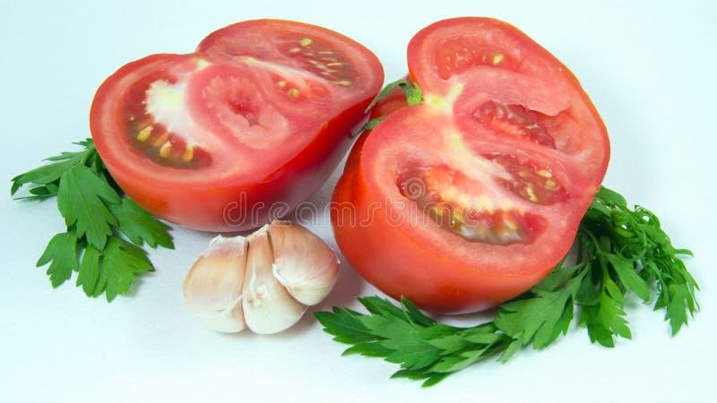 Tomates rojos con ajo y perejil fotos de archivo
