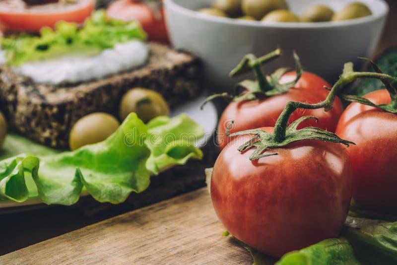 Tomates rojos en el tablero de madera y el pan con la salsa, aceitunas en cuenco en cocina imágenes de archivo libres de regalías