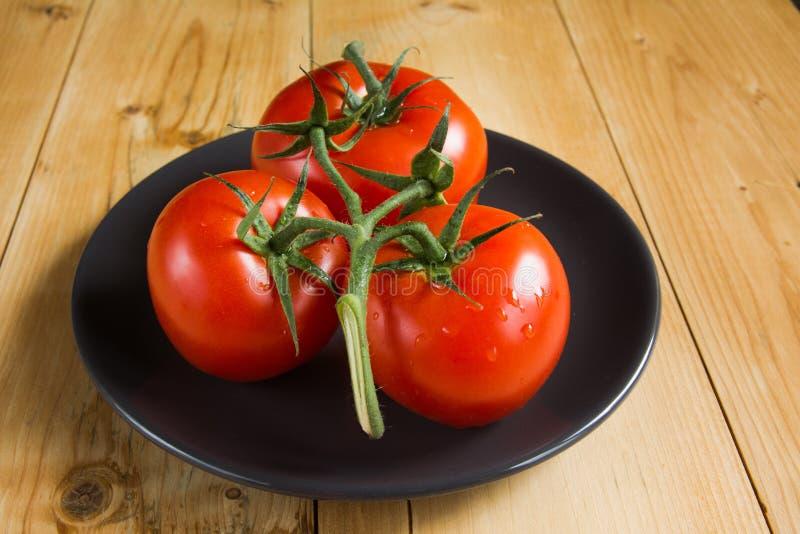 Tomates rojos en la placa negra fotos de archivo