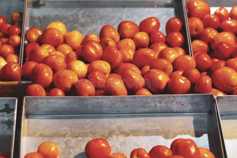 Tomates rojos en las cajas del metal en el mercado imagenes de archivo