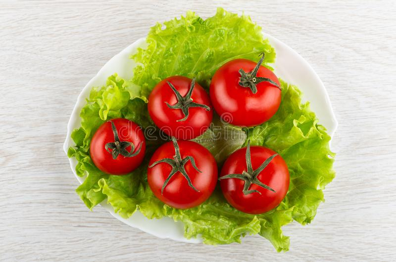 Tomates rojos en las hojas de la lechuga en plato en la tabla de madera Visi?n superior fotos de archivo