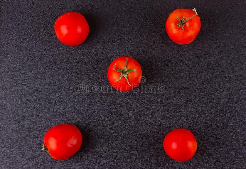 Tomates rojos en negro Visión superior foto de archivo
