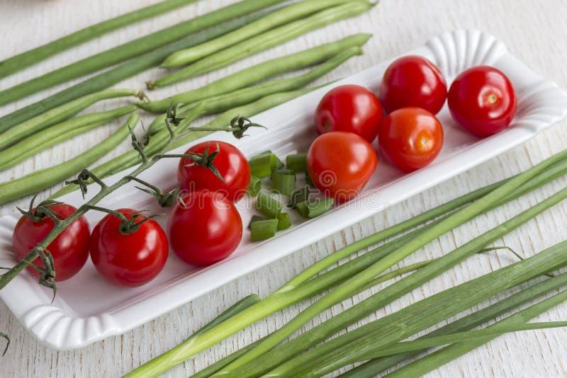 Tomates rojos en una placa blanca Cebollas y espárrago en un fondo blanco fotografía de archivo libre de regalías
