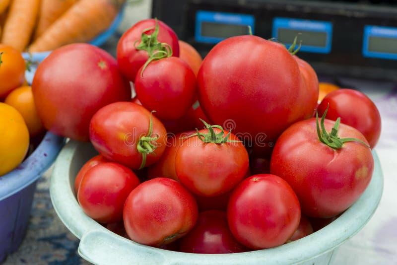Tomates rojos en una placa plástica en el contador para la venta foto de archivo