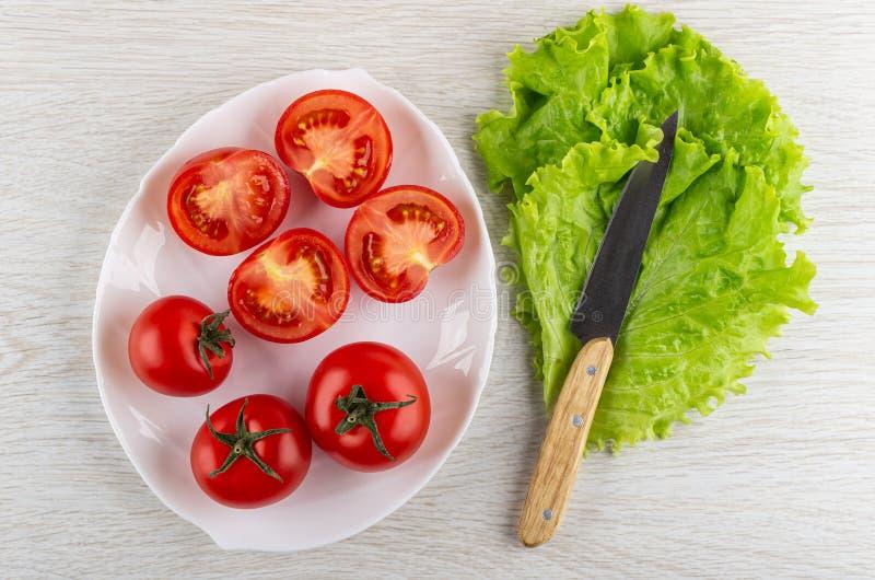Tomates rojos enteros, pedazos de tomate en el plato, cuchillo en las hojas de la lechuga en la tabla Visi?n superior imagen de archivo