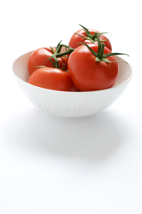 Tomates rojos jugosos en un tazón de fuente imagen de archivo libre de regalías