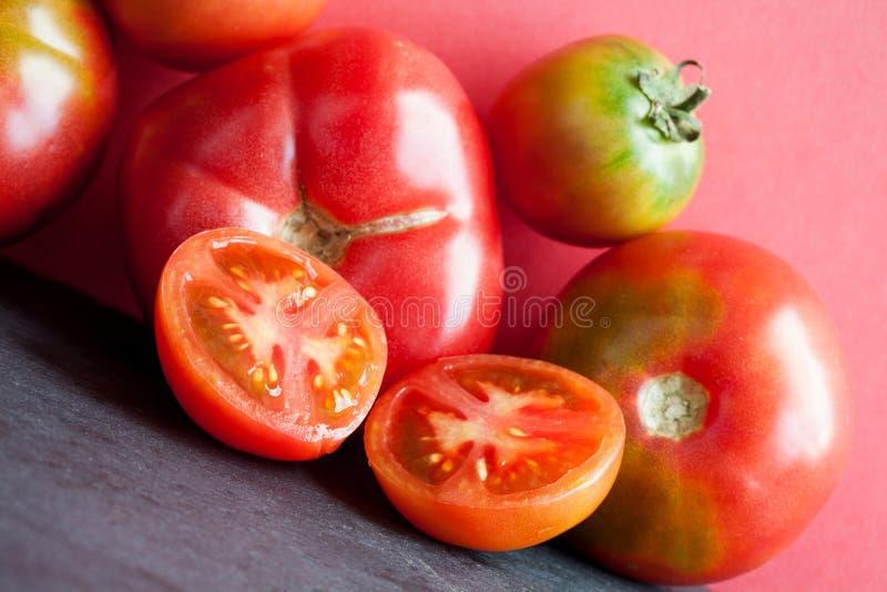 Tomates rojos maduros frescos de la visión macra Verduras orgánicas en fondo rosado foto de archivo