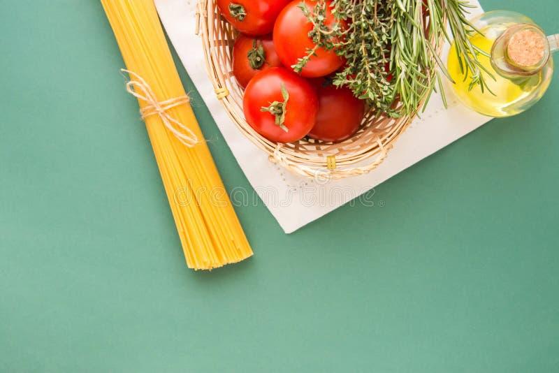 Tomates rojos maduros frescos Rosemary Thyme en la cesta de mimbre Olive Oil en espaguetis de la botella en el fondo blanco del v imagenes de archivo