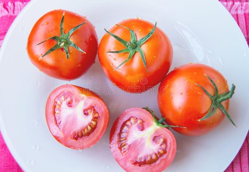 Tomates rojos maduros maduros frescos y cortar el tomate con descensos del agua y el ped?nculo verde en la placa blanca - visi?n  imagen de archivo libre de regalías