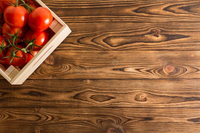 Tomates rojos maduros jugosos en un cajón de madera imagenes de archivo