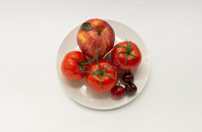 Tomates rojos, manzana, cereza dulce en una placa blanca, un aislador imagen de archivo libre de regalías