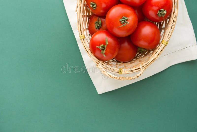 Tomates rojos orgánicos maduros frescos en cesta de mimbre en el fondo blanco del verde de la servilleta Imitación de los colores imágenes de archivo libres de regalías